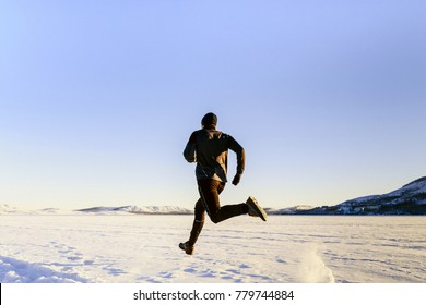 rear view athlete runner running on snow in black sport clothes