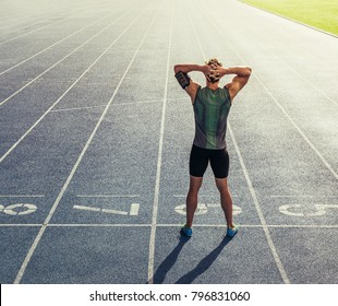 Rear view of an athlete standing on a running track with hands at the back of head. Runner getting ready to run standing at the start line on race track.