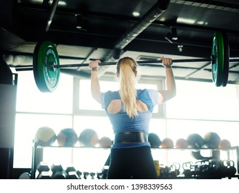 Rear view of athletic woman with blonde ponytail lifting barbell with weight plates in sunlight during workout in gym