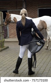 Rear view of an attractive blond woman holding a black leather saddle with her Skewbald horse. In a stableyard. November 2017