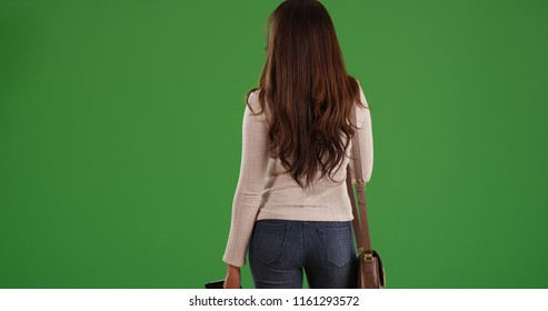 Rear view of attractive Latina woman with long brown hair on green screen