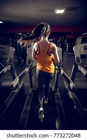 Rear view of attractive shape young sporty fitness girl with a ponytail running on the treadmill in the modern gym at night.