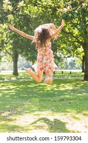 Rear view of attractive stylish brunette jumping in the air in a park on a sunny day