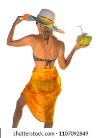 Rear view of attractive and tanned woman with yellow sarong and wide-brimmed hat while holding a coconut fresh cocktail.  Isolated on white background.