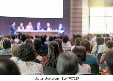 Rear view of Audience in the conference hall or seminar meeting which have Speakers are Brainstorming and talking on the stage, business and education about investment concept