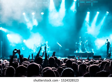 Rear view of audience crowd people fans raising hands shooting enjoying live music festival concert event concept rock band silhouettes performance sing on night club outdoor stage in spotlight light