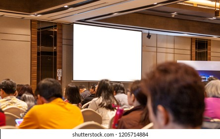 Rear view of Audience in the lecture hall or Seminar Meeting, Business ,Education, Investment with blank white screen display on background