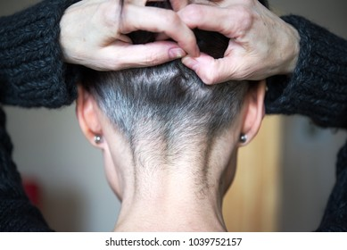 Rear view of the back woman`s head with grey hair, her hands hold and lift her hair, bare the back of neck. Close-up photo