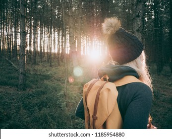Rear view of backpacker woman walking in forest