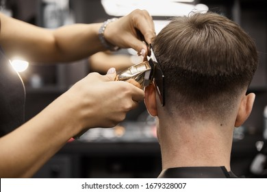 Rear view of barber girl is doing haircut, DOF