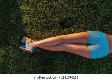 Rear view of bare legs of lying girl on grass in teal shorts and canvas trainers and tablet computer lying near on grass, backlit by sun