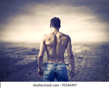 Rear view of a bare-chested muscular young man with dried up landscape