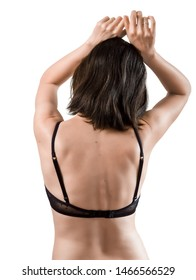 Rear view of beautiful brunette woman in sexy black lingerie raising hands up and posing in studio on white background.