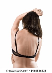 Rear view of beautiful brunette woman in sexy black lingerie raising her hand up and posing in studio on white background.