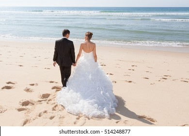 A rear view of a beautiful couple on the beach in wedding dress