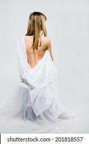 Rear view of beautiful european blond young woman is sitting on white background wearing white cloth with bare back and shoulder