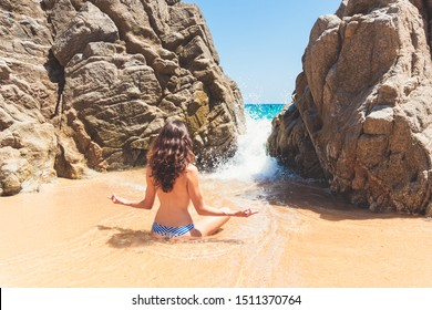 Rear view of a beautiful girl sitting on the private beach and meditating topless - mindfulness, freedom, luxury lifestyle and no bra concept