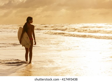 Rear view of beautiful sexy young woman surfer girl in bikini with white surfboard on a beach at sunset or sunrise