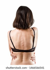 Rear view of beautiful slender brunette woman in black lace underwear, embracing herself with hands, isolated on a white background.