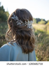 Rear view of beautiful woman with hairstyle wearing blue dress and crystal beads hair accessory in summer field at sunset