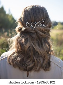 Rear view of beautiful woman with hairstyle wearing pearl hair accessory in summer field at sunset