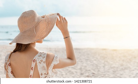 Rear view of beautiful woman holding her straw hat and wearing casual dress  while standing, enjoying and relaxing on the beach in summer vacation. sunflare light.