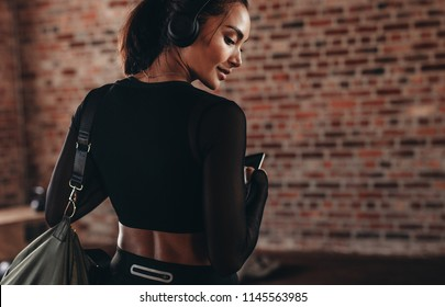 Rear view of beautiful woman in sportswear wearing headphones carrying a sports bag in gym. Fitness woman at health club.