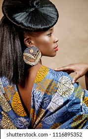 Rear view of a beautiful young African woman with an exotic hairstyle wearing stylish jewelry and clothing standing against a brown background