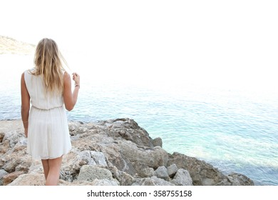 Rear view of a beautiful young blond woman on a rocky beach contemplating the blue sea on a summer holiday, relaxing in nature beauty outdoors. Travel and relaxing lifestyle. Serene adolescent space.