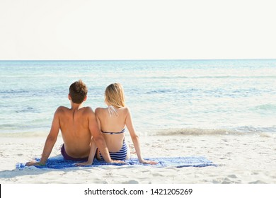 Rear view of beautiful young couple sitting on beach together contemplating the blue sea with arms interlinked, sunny vacation outdoors. Travel coastal destination leisure recreation lifestyle.