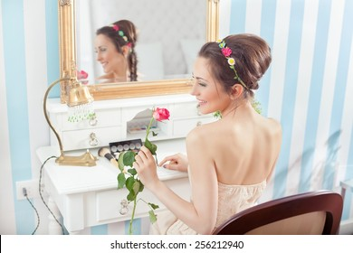 Rear view of beautiful young woman sitting in front of the mirror holding and smelling rose.