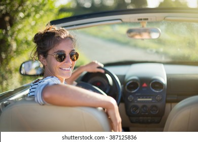 Rear view. Beautiful young woman happy to drive her convertible car on a country road in summer. she looks at camera. Shot with flare