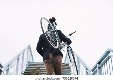 Rear view of bicycle rider carrying bike on his shoulder