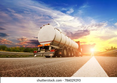 Rear view of big metal fuel tanker truck shipping fuel on the countryside road against night sky with sunset