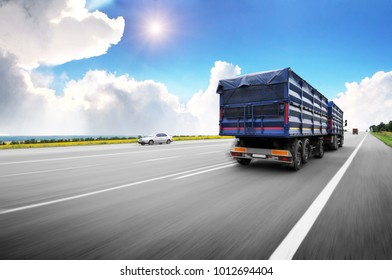 Rear view of the big truck driving fast with blue trailer on the countryside road against blue sky with clouds