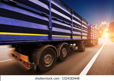 Rear view of the big truck driving fast with blue trailer on the countryside road against night sky with sunset