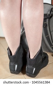 Rear view at the black motorcycle safety boots with female legs, close up