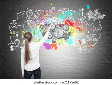 Rear view of a blond woman drawing a large and colorful brain sketch with gears on top of it on a blackboard with a business scheme on it.