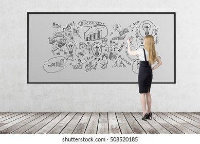 Rear view of blond woman who is drawing business sketches on whiteboard. Concept of business education.