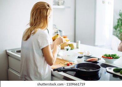 Rear view of blonde woman in white t-shirt preparing food for culinary blog. Young bloger female giving masterclass of cooking healthy food on kitchen