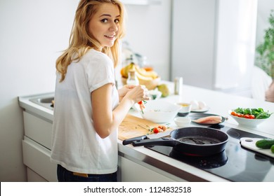 Rear view of blonde woman in white t-shirt preparing food for culinary blog. Young bloger female giving masterclass of cooking healthy food on kitchen.