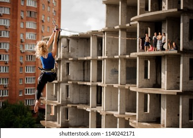 Rear view blondie woman bangling on the slackline rope on the background of house and unfinished building