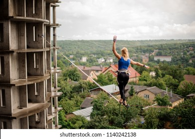 Rear view blondie woman making step on the slackline rope on the background of houses among trees and clear sky