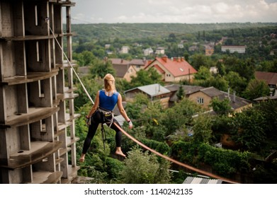 Rear view blondie woman sitting on the slackline rope between the unfinished buildings on the background of houses among trees