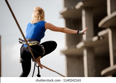Rear view blondie woman sitting on the one leg on the slackline rope on the background of unfinished building
