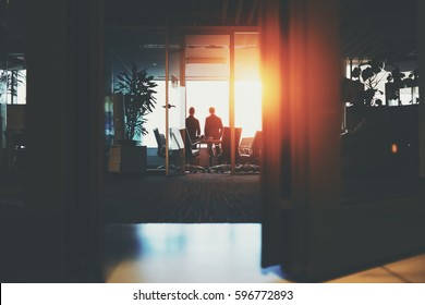 Rear view from bottom through half-closed doors of silhouettes of two young businessmen near big window in dark office interior after meeting having rest, discussing something and looking outside