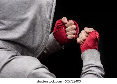 Rear view of boxer clenching fists wrapped with red tapes isolated on black