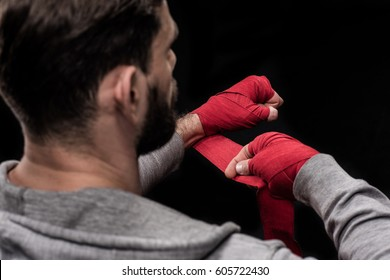 Rear view or boxer wrapping hands with red tape  isolated on black