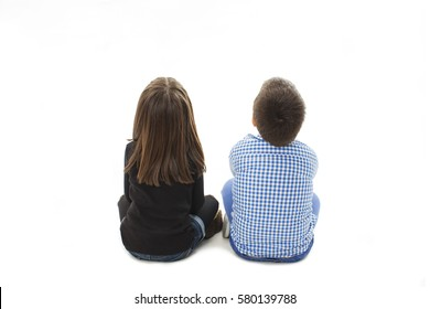 Rear view of boy and girl looking up, sitting on floor. Isolated on white background