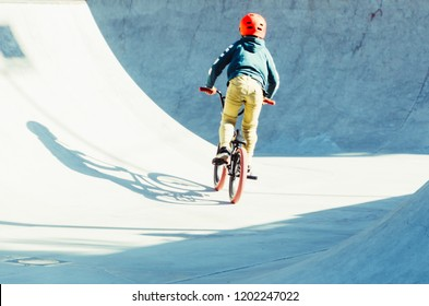 rear view of a boy pedaling in his bicycle in a bmx park